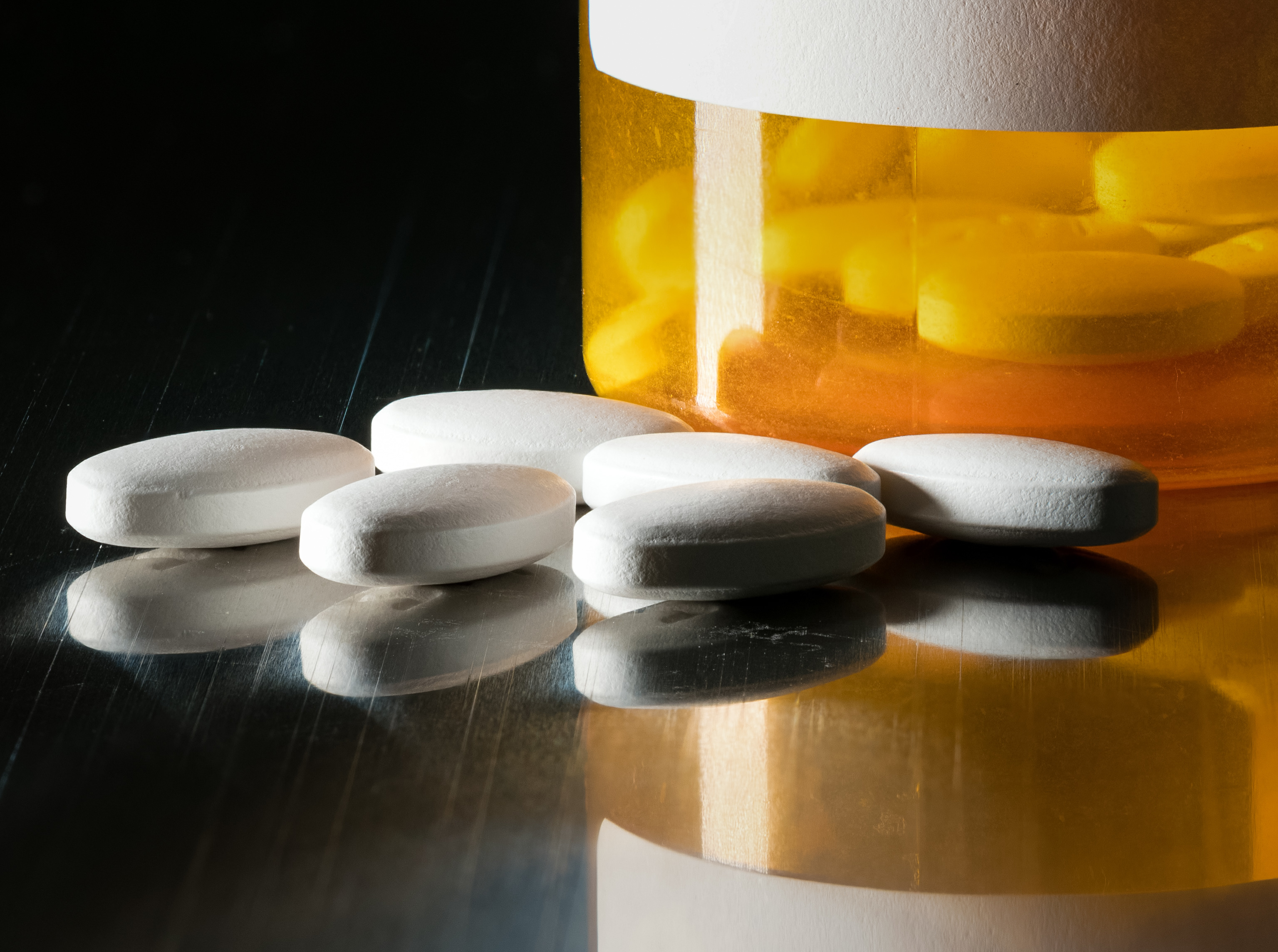Prescription bottle with blank label for copy space and white pills or tablets on metal table for opioid epidemic illustration