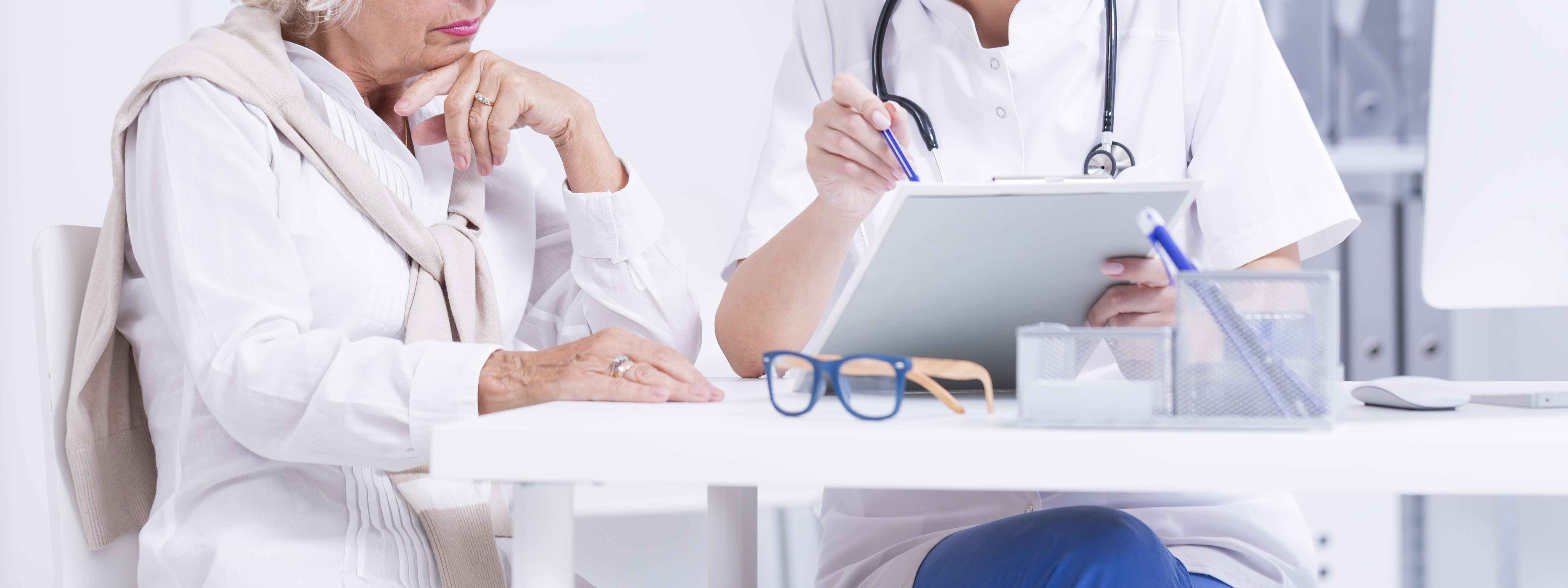 Panoramic shot of a female doctor explaining results of a blood test to her elderly patient