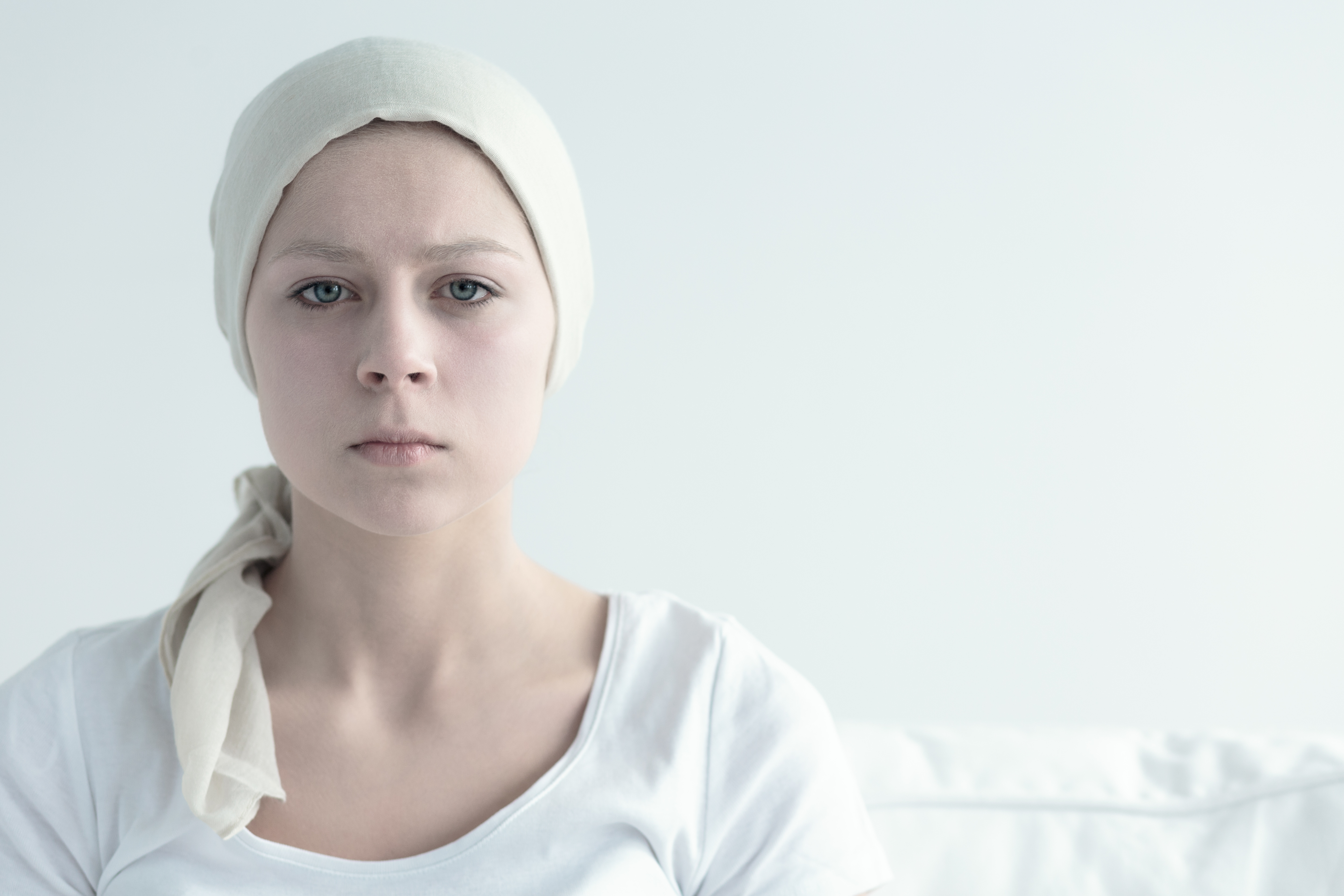 Girl with cancer staring straight forward with a serious look in her eyes