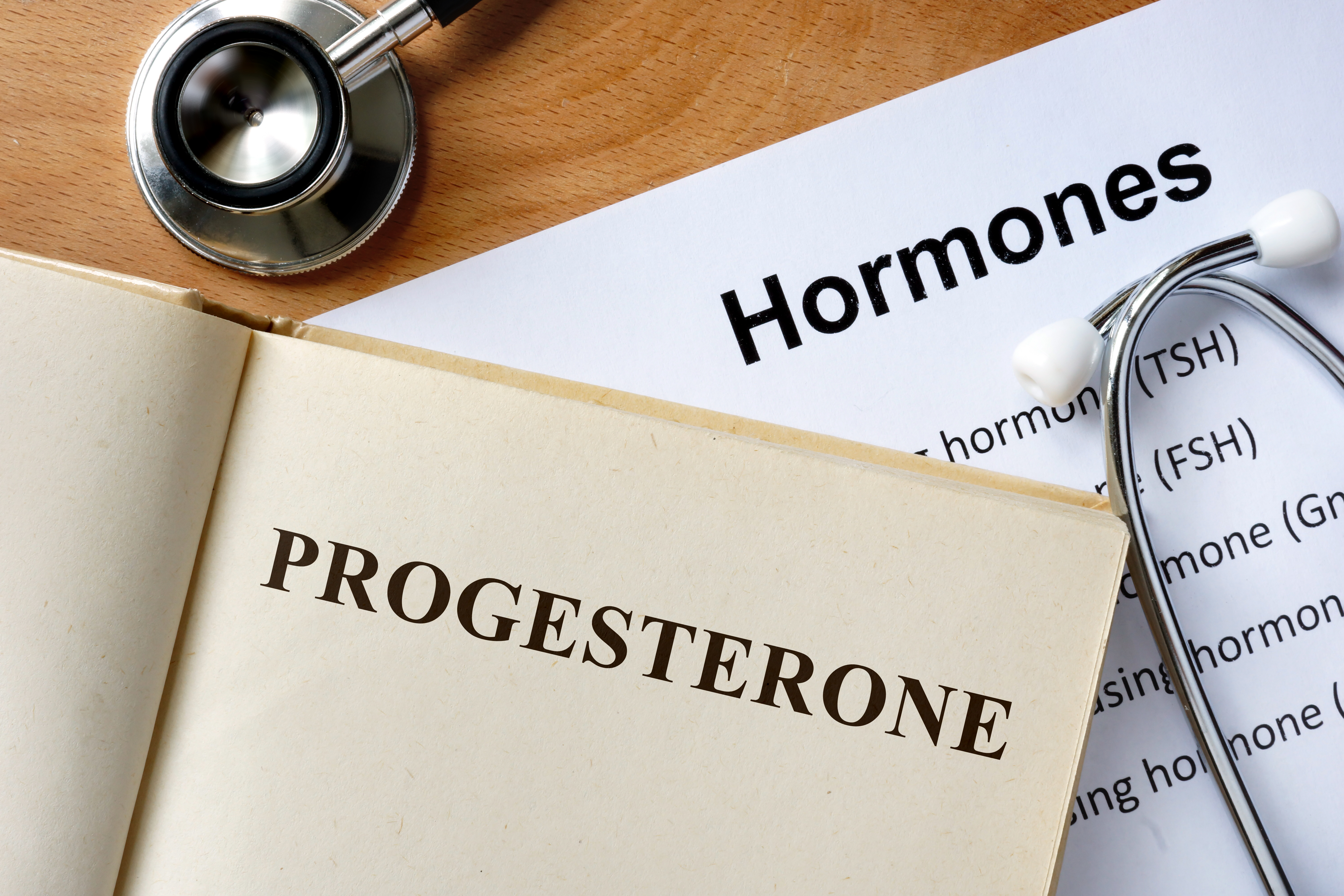 Progesterone  word written on the book and hormones list.