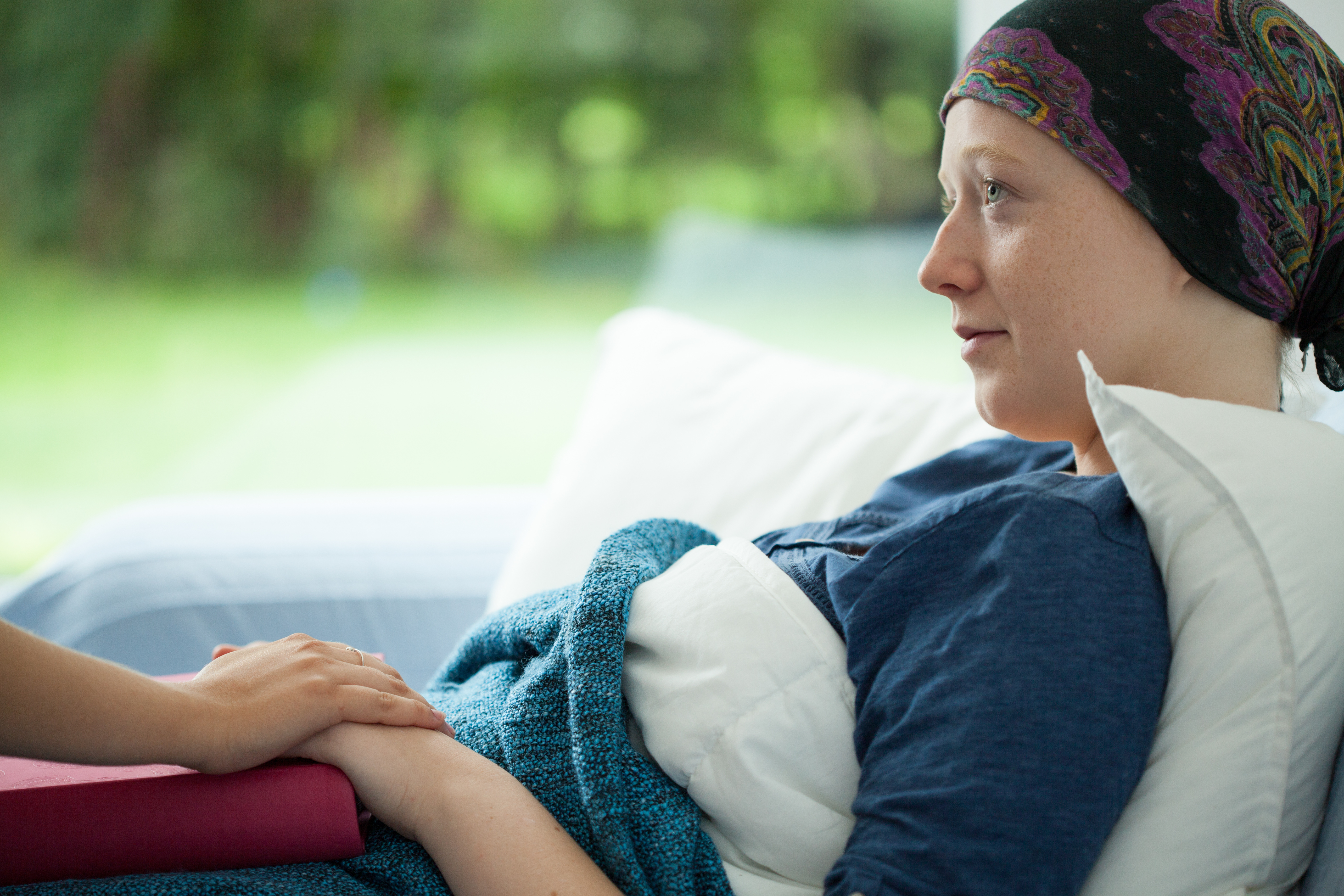 Cancer woman lying in bed supported by mum