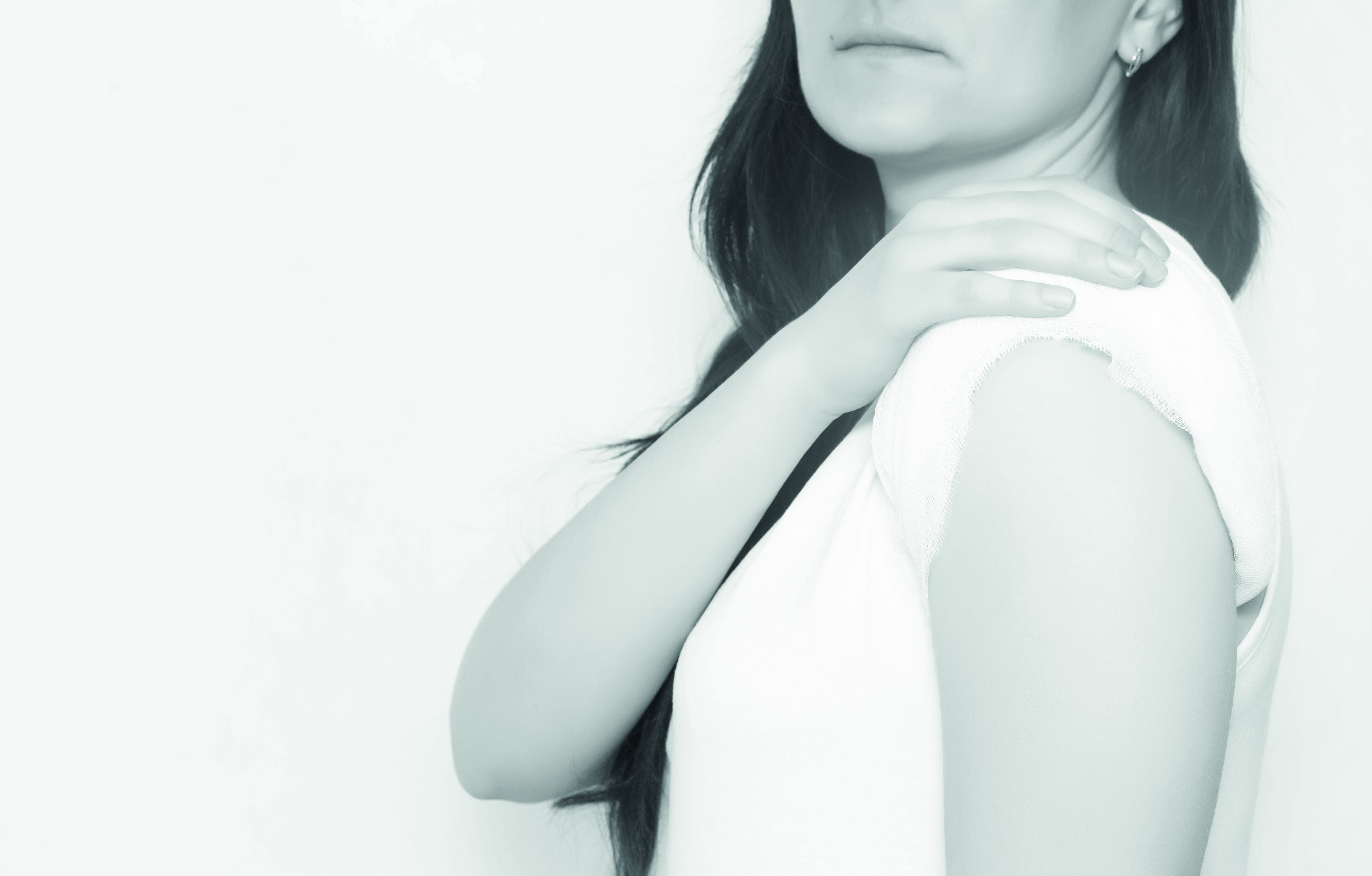 The girl holds on to the sore shoulder which has a healing compress, white background, copy space, medical, polymyalgia