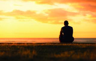 Thoughtful man sitting watching the sunset.