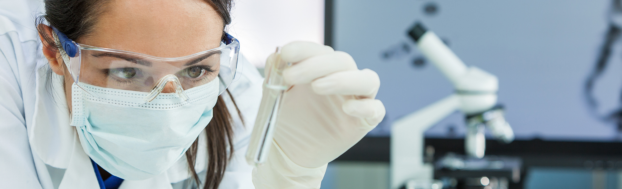 Panoramic web banner female medical or research scientist or doctor using looking at a test tube of clear solution in a lab or laboratory. Header panorama.