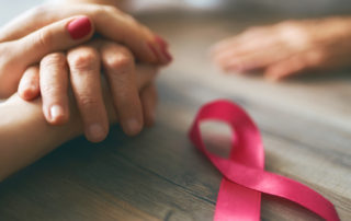 Females hands. Top view, close up. Pink ribbon like a symbol of Breast Cancer Awareness.