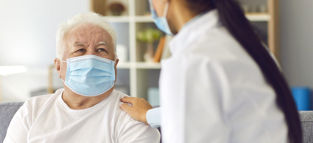Doctor and patient in face masks. Website header, copy space. Physician visiting senior man at home during period of seasonal infection or Covid 19 pandemic, supporting, giving hope, cheering him up